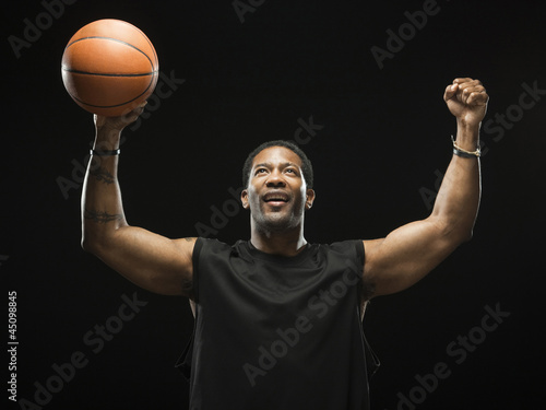 Mid adult man celebrating with basketball