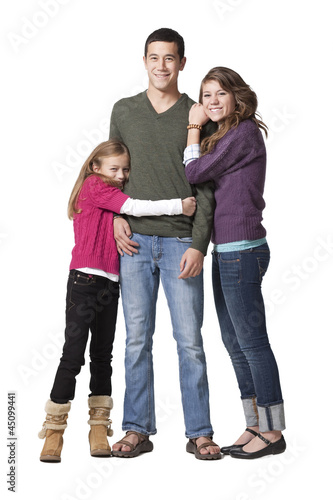 """Portrait of young man with teenage girl (16-17) and primary age girl (8-9), studio shot"""