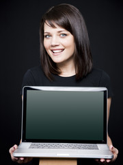 """Young woman showing laptop, studio shot"""