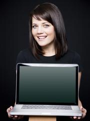 """""""Young woman showing laptop, studio shot"""""""