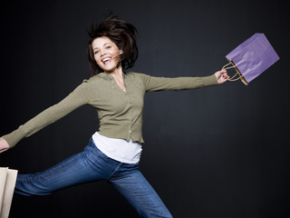 """Young woman with shopping bags jumping, studio shot"""