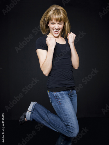 """Young cheerful woman jumping, studio shot"""