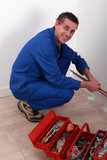 Plumber kneeling by tool box