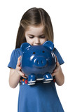 Studio shot of girl (4-5) holding piggy bank