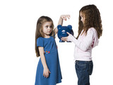 Studio shot of girl (4-5) inserting money to piggy bank held by sister (6-7)