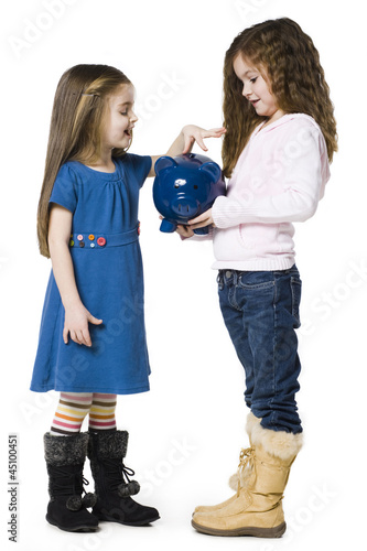 Studio shot of girl (4-5) inserting money to piggy bank held by friend (6-7)