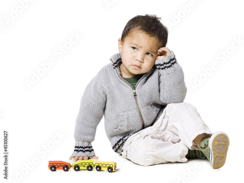 Studio portrait of boy (18-23 months) playing with toy car