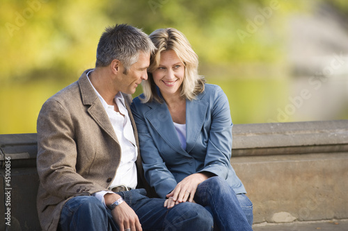 """USA, New York, New York City, couple sitting in park"""