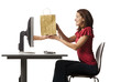 Conceptual picture of young woman receiving shopping bag out of her computer