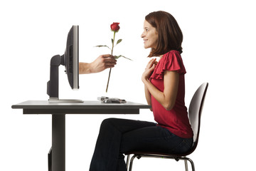Conceptual picture of young woman receiving red rose out of her computer