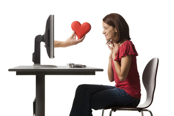 Conceptual picture of young woman receiving red heart out of her computer