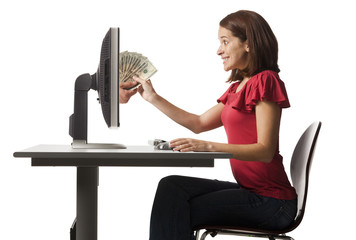 Conceptual picture of young woman receiving paper money out of her computer