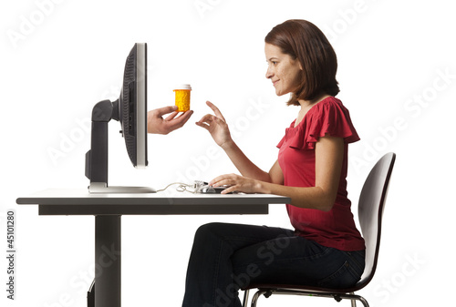 Conceptual picture of young woman receiving pill bottle out of her computer