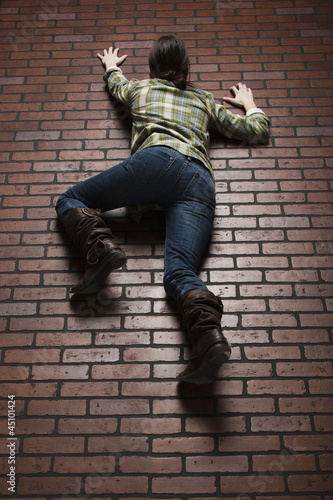 Studio shot of young woman climbing up brick wall
