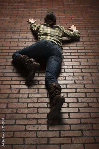 Studio shot of young woman climbing up brick wall