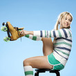 """Young woman wearing roller skates, studio shot"""