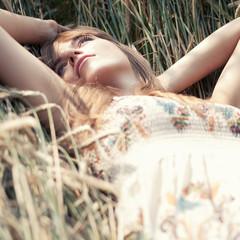 Hübsche junge Frau liegend in einem Kornfeld