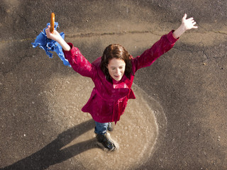Young woman standing in rain with arms outstretched