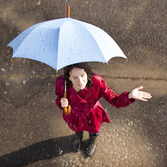 Young woman standing in rain holding umbrella