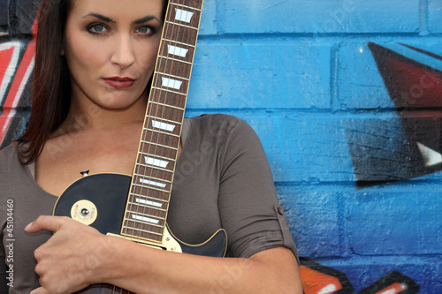 Female guitarist standing in front of graffiti