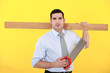 Businessman stood with saw and plank