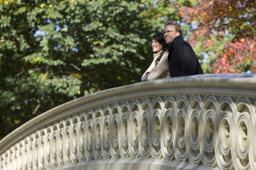 USA, New York City, Manhattan, Central Park, Mature couple standing on bridge in Central Park