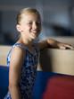 USA, Utah, Orem, portrait of girl (10-11) leaning on balance beam in gym