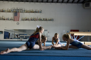USA, Utah, Orem Girls (8-11) stretching in gym