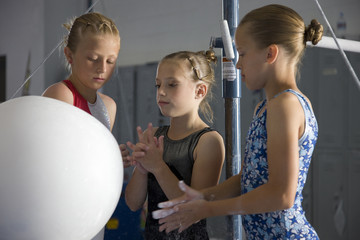 USA, Utah, Orem, girls (8-11) in gym applying talcum powder to hands