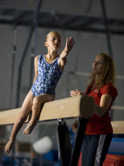USA, Utah, Orem, girl (10-11) exercising on balance beam with teacher