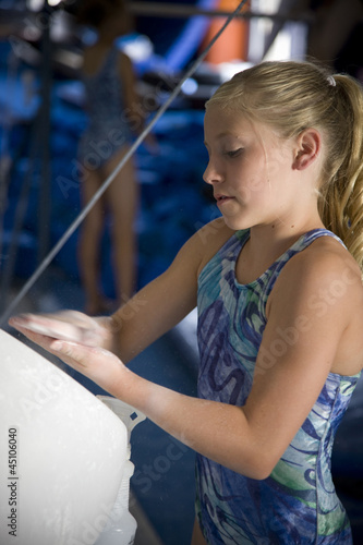 USA, Utah, Orem, girl (10-11) in gym applying talcum powder to hands