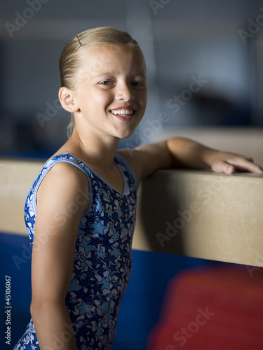 USA, Utah, Orem, portrait of girl (10-11) leaning on balance beam in gym