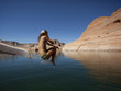 """USA, Utah, Young woman jumping into Lake Powell"""