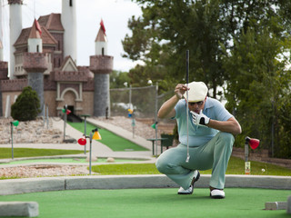 """USA, Utah, Orem, Man lining up shot on miniature golf course"""