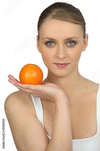 Blond woman with orange in hand