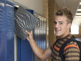 """USA, Utah, Spanish Fork, Portrait of school boy (16-17) taking file from locker"""