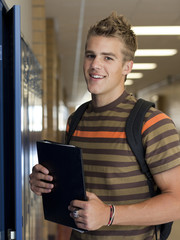 """USA, Utah, Spanish Fork, Portrait of school boy (16-17) holding file in corridor"""