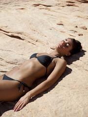 """""""USA, Utah, Lake Powell, Young woman sunbathing on rock"""""""