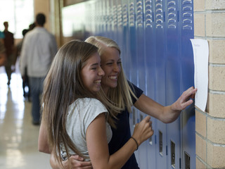 """USA, Utah, Spanish Fork, Two school girls (14-17) embracing in corridor"""