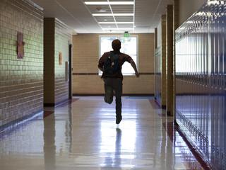 """USA, Utah, Spanish Fork, School boy (16-17) running in corridor"""
