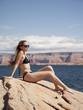 """USA, Utah, Lake Powell, Young woman wearing bikini sunbathing and looking away"""