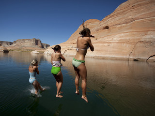 """USA, Utah, Lake Powell, Three women jumping into lake"""