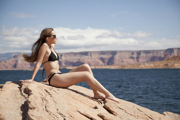 """USA, Utah, Lake Powell, Young woman wearing bikini sunbathing and looking away"""