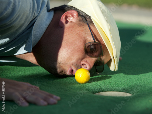 """USA, Utah, Orem, Man blowing air to push golf ball"""