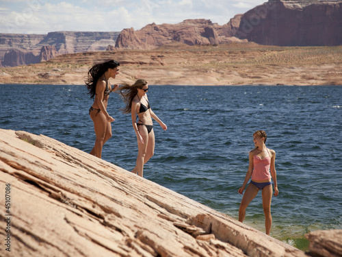 """USA, Utah, Lake Powell, Three young women in bikini on lakeshore"""
