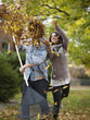"""USA, Utah, Provo, Young woman throwing leaves over husband in garden"""