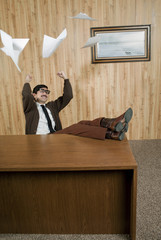Successful businessman throwing paperwork in office