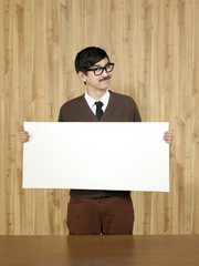 Studio portrait of businessman holding blank placard