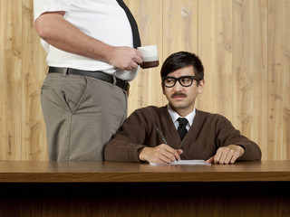 Boss by smug businessman at desk in office