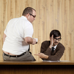 Businessman ignoring colleague at desk in office
